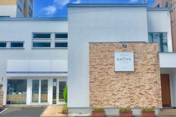 レンガの壁と白い建物が印象的なパティスリーシイヤの写真