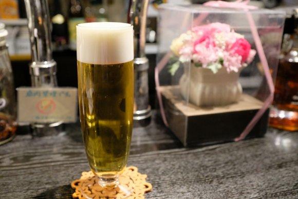 WINE & CAFE Kanakoyaのビールとカウンターに飾られているお花のディスプレイの写真