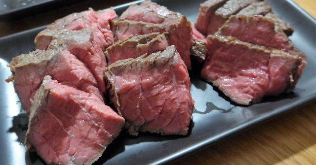 黒い皿の上に肉が置かれている