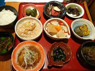 おばんざい含めた小皿が9つ綺麗に並んでいるとなりにご飯と味噌汁が置いてある写真