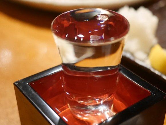 枡に置かれたグラスに日本酒溢れるほどいっぱい