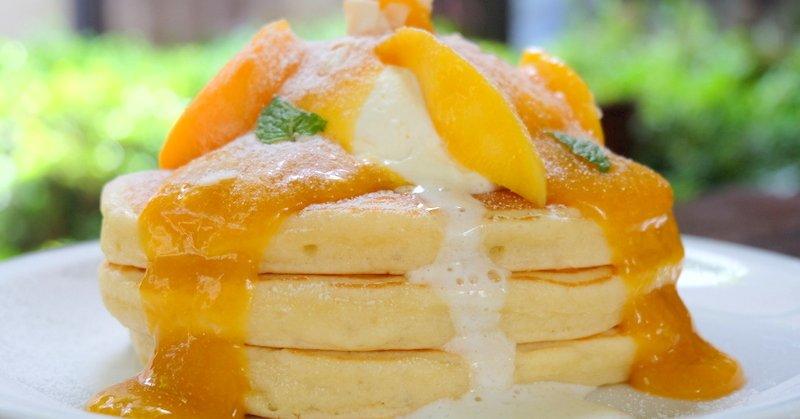 マンゴーシロップがかかった三枚重ねのパンケーキ