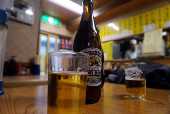 昔ながらの店内で机の上にビール瓶と注がれたグラスが置かれている