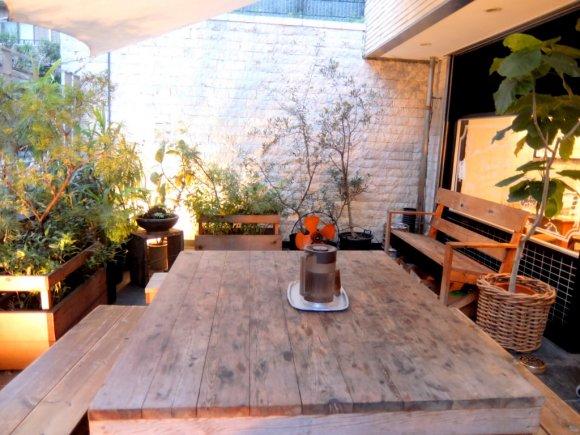 緑につつまれた店外にテーブルが設置されている