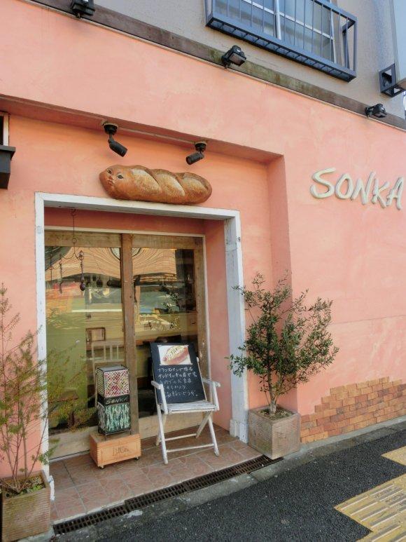 くすんだオレンジの外壁が印象的な店の外観の写真