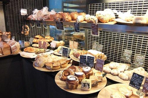 丸い木のテーブルに可愛らしいサワムラのパンが並んだ写真